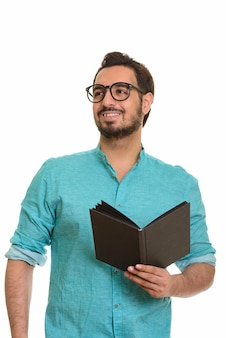Young happy indian man holding book while thinking