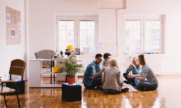 円のオフィスの床に座って、喜びでブレーンストーミングする若い幸せな革新的なビジネス人々。チームワークと一体性の概念。