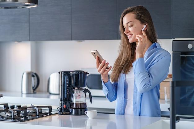 自宅のキッチンで白いワイヤレスイヤホンとスマートフォンを使用して若い幸せなうれしそうな女性リスニングオーディオブック。モバイルピープル