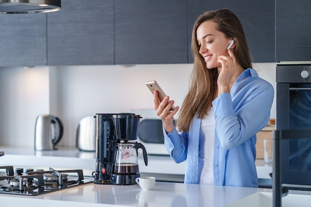 Young happy joyful female listening audio book using white wireless earphones and smartphone in the kitchen at home. mobile people