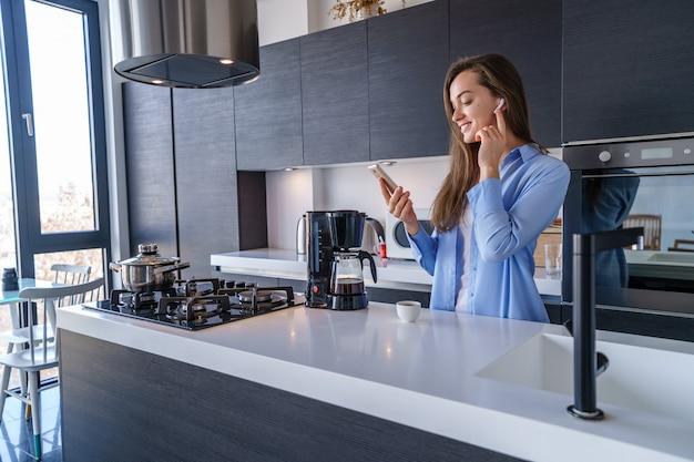 若い幸せなうれしそうな女性が自宅のキッチンで白いワイヤレスイヤホンとスマートフォンを使用して音楽を聴きます。モバイルピープル