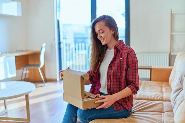 Молодая счастливая, радостная улыбающаяся девушка-клиент получила посылку и распаковку картонной коробки с заказом в интернет-магазине, хорошая служба доставки
