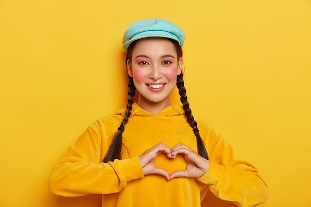 Молодая счастливая кореянка делает жест над грудью, имеет две косички, носит синюю кепку и желтую толстовку, выражает хорошие эмоции