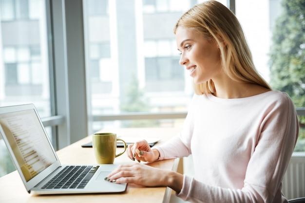 Молодая счастливая дама сидит в офисе коворкинг