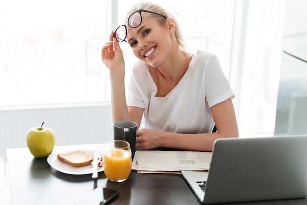 若い幸せな女性はメガネを脱ぐし、キッチンで探しています
