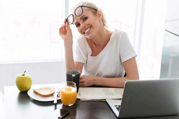 Young happy lady take off glasses and looking in kitchen