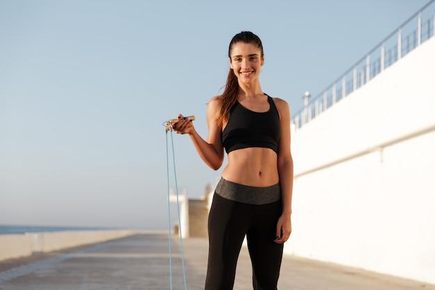 縄跳びで海の近くのトレーニング若い幸せな女性