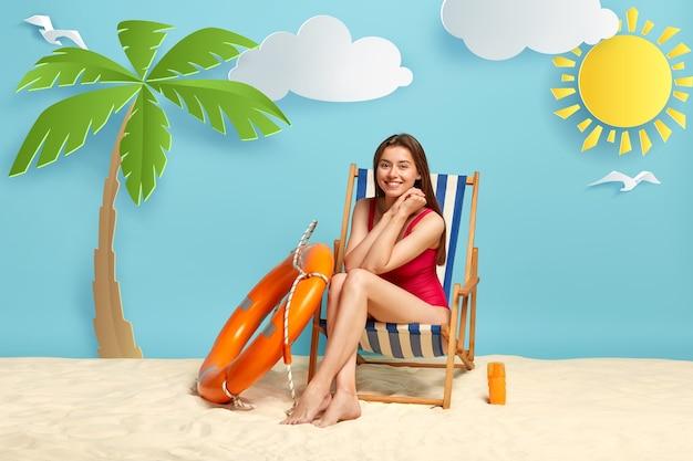 La giovane signora felice indossa un bikini rosso, si rilassa sulla sedia a sdraio in spiaggia durante una calda giornata di sole, gode di vacanze al mare, sorride volentieri