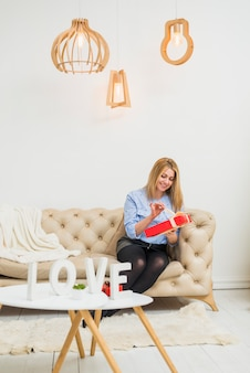 Young happy lady with gift box on sofa near table with love sign