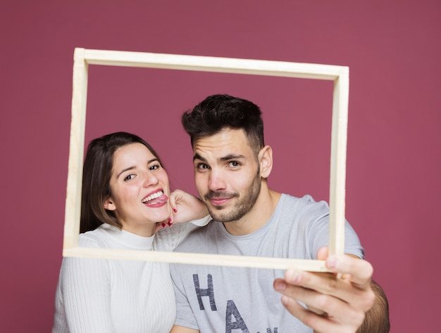 Young happy lady with hand on shoulder of positive guy holding photo frame