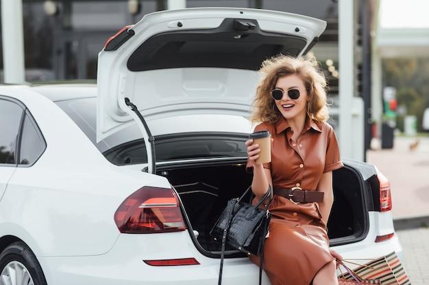 Молодая счастливая дама с хозяйственными сумками и кофе возле машины на открытом воздухе