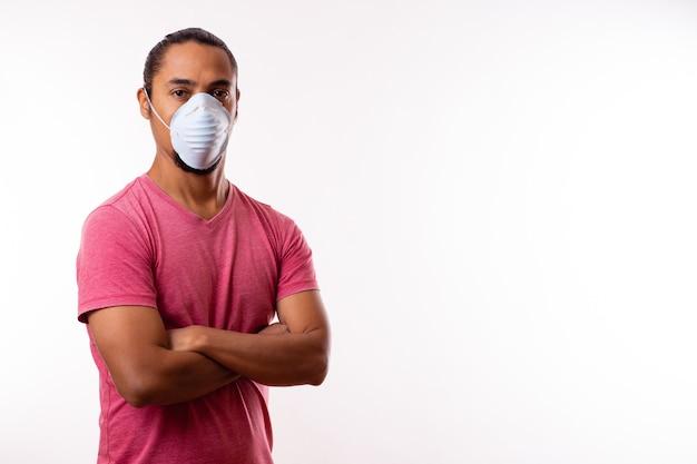 医療マスクを持つ若い幸せなラテン男。スペースをコピーします。コロナウイルスの概念。