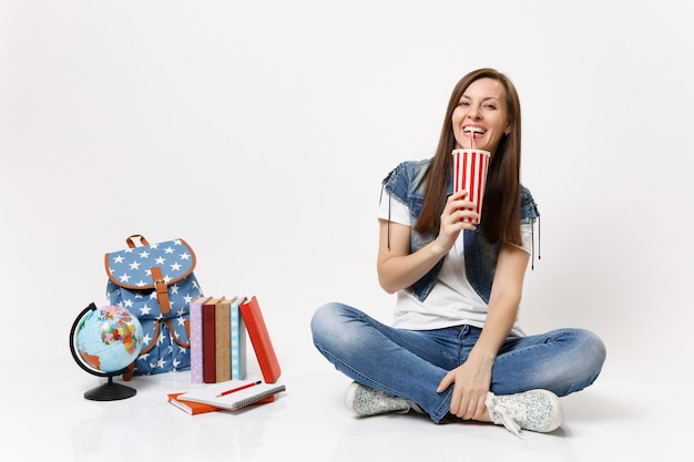 Young happy laughing woman student holding plastic cup of soda or cola drinking sitting near globe, backpack, school books isolated