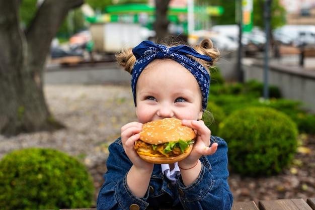 Молодая счастливая маленькая девочка ест гамбургер в кафе на открытом воздухе