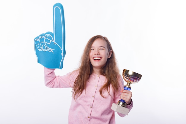 Young happy little girl is wearing fan glove and holding a winner trophy.