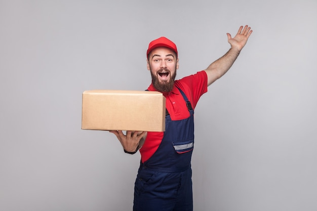 Young happy logistic delivery man with beard in blue uniform and red t-shirt standing, holding cardboard box and toothy smiling on grey background. indoor,studio shot, isolated,copy space
