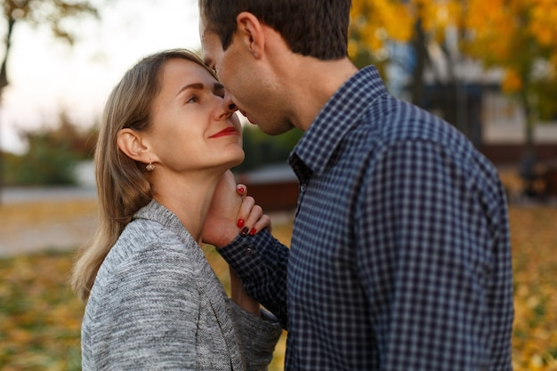 Молодые счастливые влюбленные обнимаются и целуются на открытом воздухе