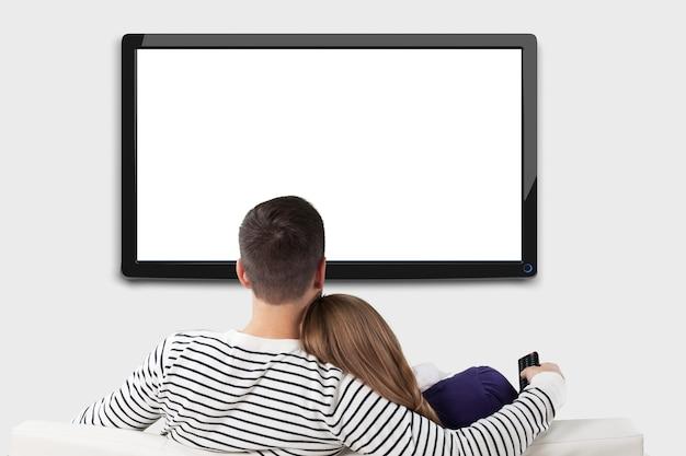 Молодые счастливые влюбленные, сидя на диване в помещении и смотря телевизор.