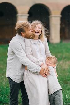 雨の中で抱き締める若い幸せな愛情のある家族。雨滴の子供と一緒にリネンの衣装を着た本物の家族
