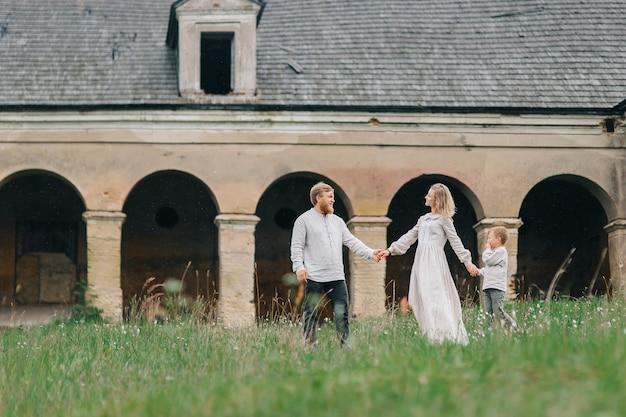 若い幸せな愛情のある家族が一緒に手をつないで歩きます。男の子とリネンの衣装を着た家族。環境にやさしい服のファッションコンセプト。