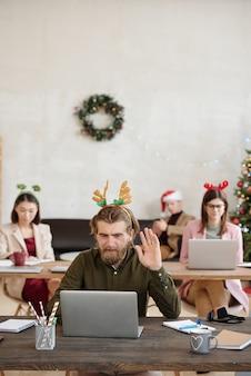 직장에서 온라인 커뮤니케이션 중에 고객에게 인사하는 동안 노트북 디스플레이를 보고 손을 흔드는 젊은 행복한 남성 사무실 관리자