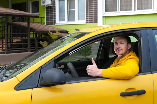 젊은 행복한 남성 택시 운전사는 택시 운전대 뒤에 앉아서 다음과 같이 보여줍니다.