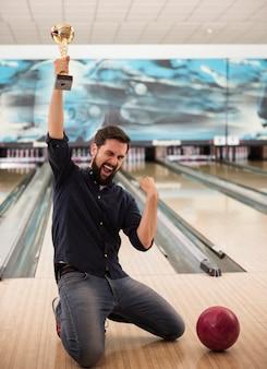 Giovane uomo felice dopo aver vinto al bowling