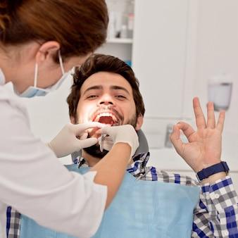 Молодой счастливый мужчина и женщина в стоматологическом осмотре у стоматолога