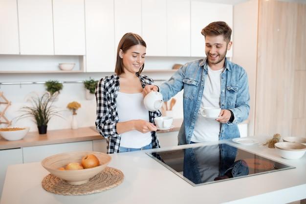 Молодой счастливый мужчина и женщина на кухне, завтрак, пара вместе утром, улыбаясь, пьют чай