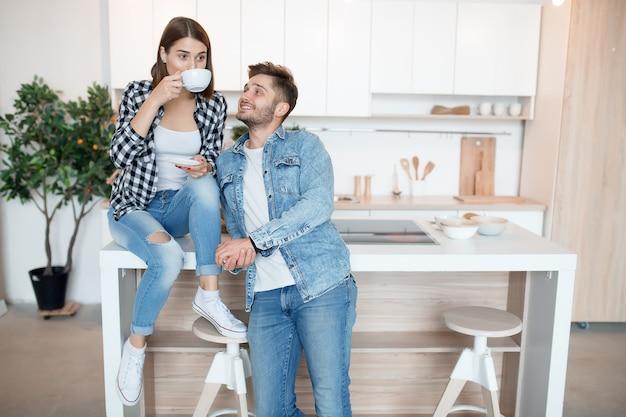 若い幸せな男と女のキッチン、朝食、朝一緒にカップル、笑顔、お茶