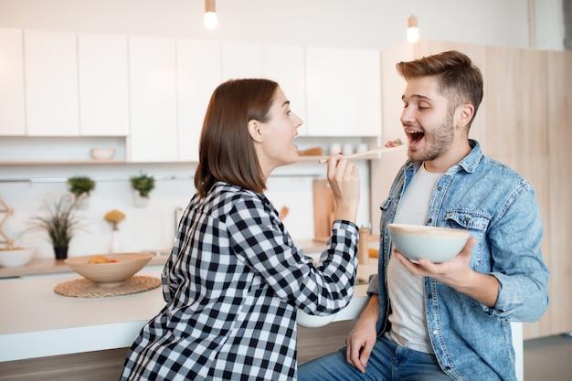 若い幸せな男と台所で女性、朝食を食べる、朝一緒にカップル、笑顔