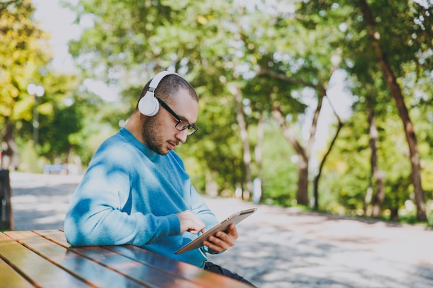 若い幸せな男、ビジネスマン、または学生がヘッドフォンでテーブルに座っているカジュアルな青いシャツのメガネ、都市公園でタブレットpc、音楽を聴き、緑の自然で屋外で休憩します。ライフスタイルのレジャーの概念。