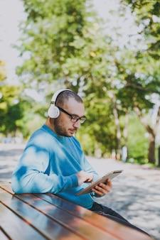 Молодой счастливый человек, бизнесмен или студент в повседневных очках с синей рубашкой, сидя за столом с наушниками, планшетным пк в городском парке, слушает музыку, отдыхает на открытом воздухе на зеленой природе. концепция досуга образа жизни.