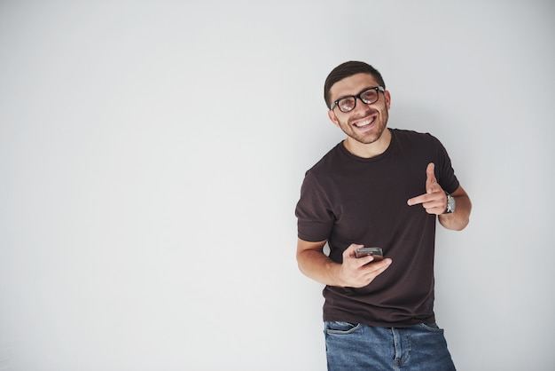 白のスマートフォンを着てカジュアルな若い幸せな男