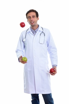 Young happy man doctor smiling while juggling green apple and two red apples