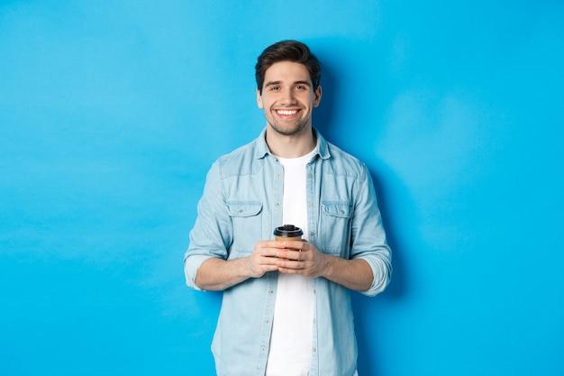 Молодой счастливый человек пьет кофе из кафе на вынос, доволен улыбаясь, стоя на синем фоне