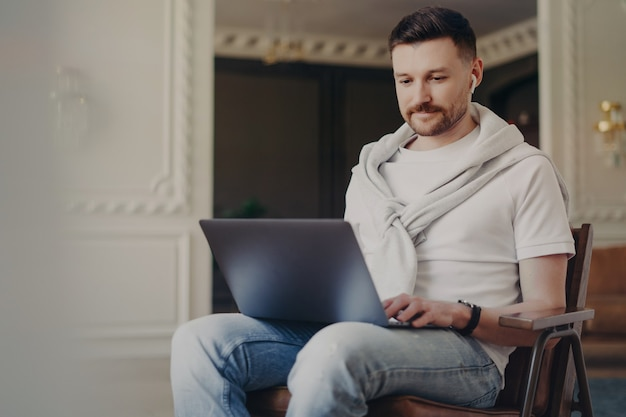 Young happy man freelancer in casual clothes wearing earphones using laptop while working from home, listening to music and looking at computer screen while sitting at modern home office interior