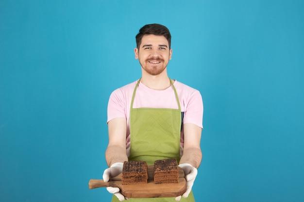 木の板に新鮮なチョコレートケーキのスライスを保持している若い幸せな男。