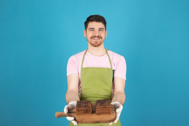Giovane uomo felice che tiene le fette di torta al cioccolato fresco sul bordo di legno.