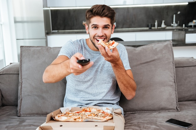 Young happy man holding remote control and pushing the button while eating pizza.