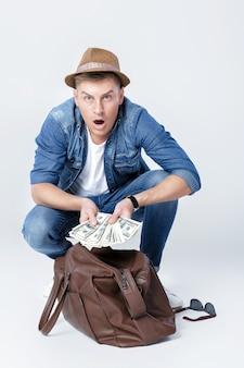 Молодой счастливый человек в шляпе нашел деньги в кожаной сумке