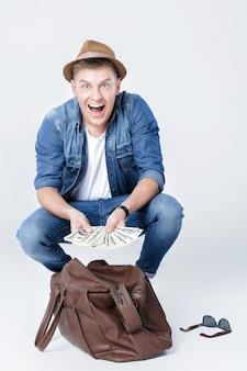 모자에있는 행복 한 젊은이 가죽 가방에서 돈을 발견