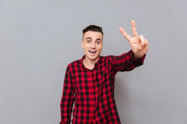 Молодой счастливый человек в рубашке, показывая мир