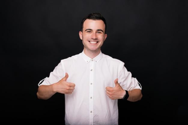 白いシャツの若い幸せな男は親指を現して、黒い背景にカメラに笑顔します。