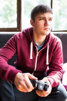 Giovane uomo felice ridendo e giocando ai videogiochi nel fine settimana