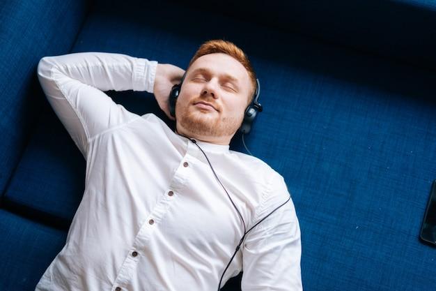 自宅のソファに横になって音楽を聴いている若い幸せな男、上面図。音楽リラクゼーションの概念。