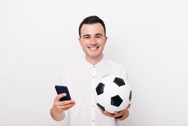 Молодой счастливый человек смотрит в камеру и держит телефон и футбольный мяч