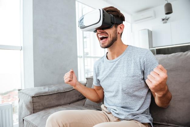 Молодой счастливый человек делает жест победителя, нося устройство виртуальной реальности и сидя на диване.