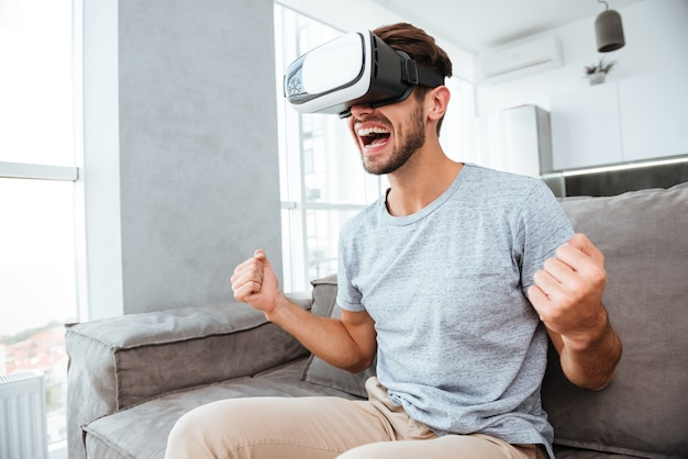 Young happy man making winner gesture while wearing virtual reality device and sitting on sofa.