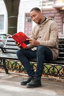거리에서 벤치에 앉아있는 동안 책을 읽고 젊은 행복한 사람